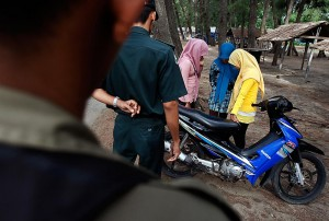 """LA Times: """"The Sharia police stop three veiled teenage girls at a beach in Banda Aceh, Indonesia, a city where Islamic religious codes of public behavior are strictly enforced. The girls' crime: wearing tights. They were told to go home immediately and change into proper attire."""""""