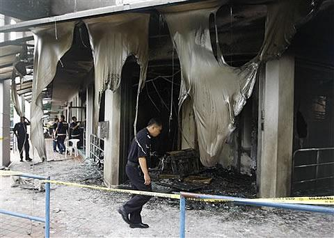 A Kuala Lumpur police officer inspects the damage to the Metro Tabernacle Church which was destroyed by a fire bomb in the Kuala Lumpur suburb of Desa Melawati,08 Jan 2010 (Photo AP)