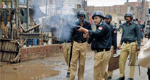 Policemen fire teargas shells to disperse the protesters during a demonstration against the killing of two Christian brothers outside the court building in Faisalabad. –Online Photo